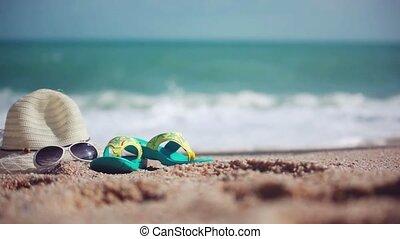 Woman on the Beach. Female feet walks along the beach and the Sea on hat, sunglasses and beach shale. 1920x1080