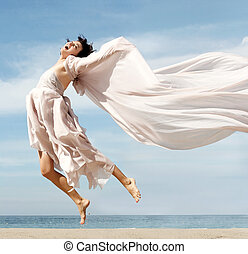 Woman on the beach - Happy woman jumping on the beach