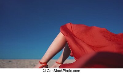 Woman on the beach in a red skirt.