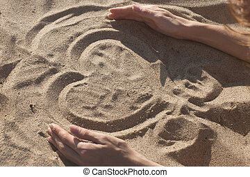 woman on the beach making heart on the sand
