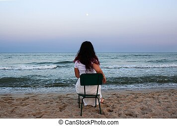 woman on the beach sitiing on a chair looking at the moon