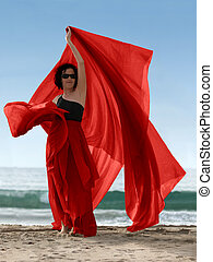 Woman on the beach with a red scarf