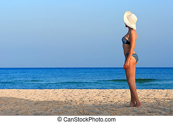 Woman on the beach with white hat