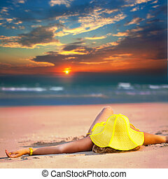 Woman in yellow hat lies on the beach