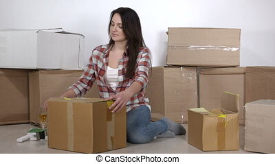 Woman on the floor in a new apartment unpacks the moving cardboard boxes