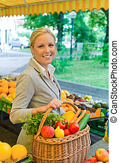 a young woman buying fruits and vegetables at a market. freshness and healthy diet.