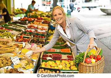 woman on the fruit market with basket - a young woman buying...
