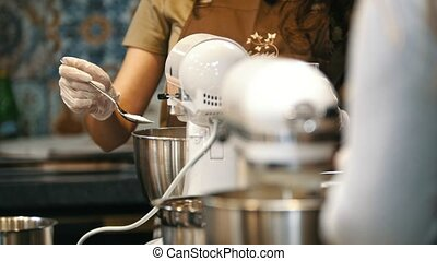 Woman on the kitchen adds sugar for meringue in mixer - Pavlova cake