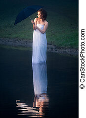 Woman on the lake bed sheet wrapped with umbrella