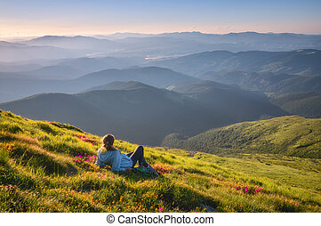 Woman on the mountain peak with green grass and pink flowers