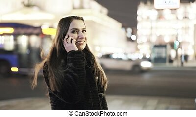 Woman on the phone in a night city