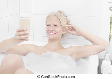 Woman on the phone in the bathtub