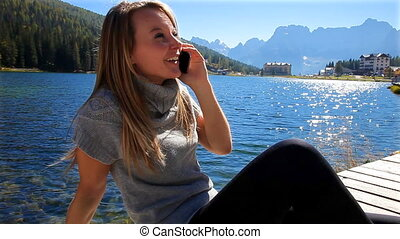 Woman on the phone in the mountain - Cute blond woman in the...
