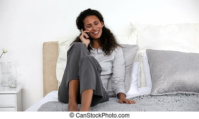 Woman on the phone lying on her bed