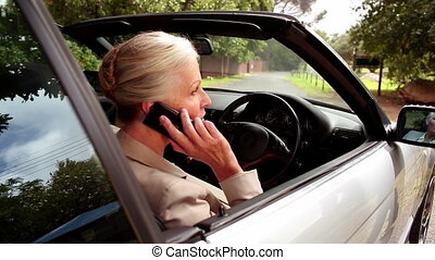 Woman on the phone sitting in her car