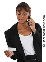 Woman on the phone watching business card