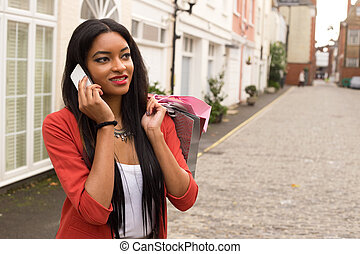 woman on the phone with shopping bags.