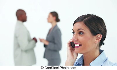 Woman on the phone with two business people in background