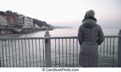 woman on the pier watching at the camera on sea