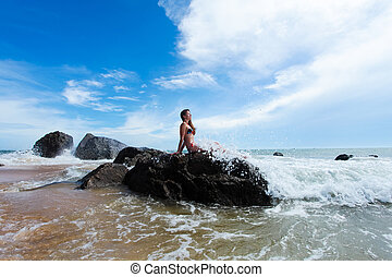 Woman on the rock in ocean