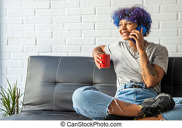 woman on the sofa at home with cup of coffee talking on mobile phone