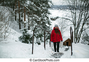 Woman on the street in the Russian village at snowy winter.