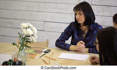 Woman on training courses drawing pencil touch a vase with flowers.