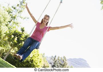 Woman on tree swing smiling