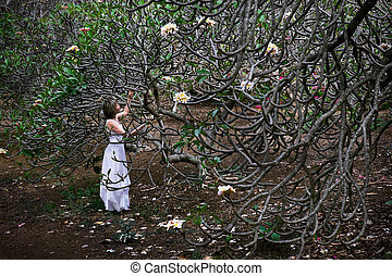 Woman on vacation by Plumeria tree with white flowers.