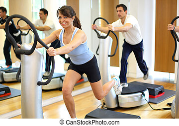 Woman on vibration plate in a gym - Group of two men and one...