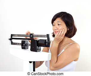 Woman on Weight Scale Worried - Cute middle age woman on...