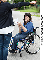 Woman on wheelchair asking a passerby about directions