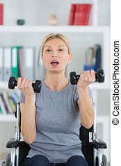 woman on wheelchair holding weights