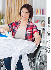 woman on wheelchair ironing