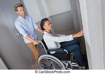 woman on wheelchair pressing elevator button