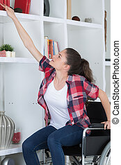 woman on wheelchair trying to reach a shelf