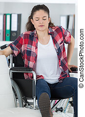 woman on wheelchair with trying to lift herself