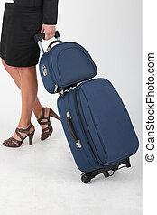 Woman on white background pulling luggage