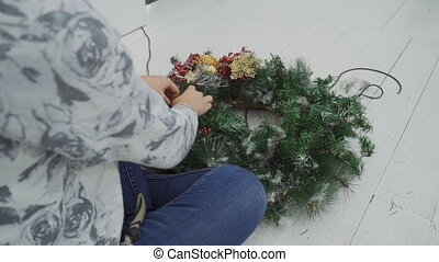 Woman on wooden floor collects Christmas tree wreath. -...