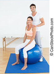 Woman on yoga ball working with physical therapist - Young...