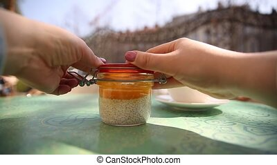 Woman open a jar with chia seeds pudding with mango mousse...