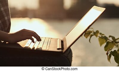 Woman open and typing on a laptop keyboard in a warm sunny day outdoors. Sunset.