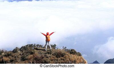 woman open arms on mountain peak - cheering hiking woman...