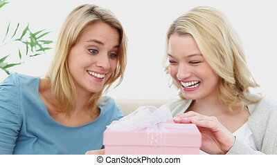 Woman opening a gift box with a friend