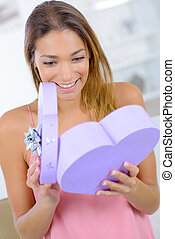 Woman opening a heart shaped gift