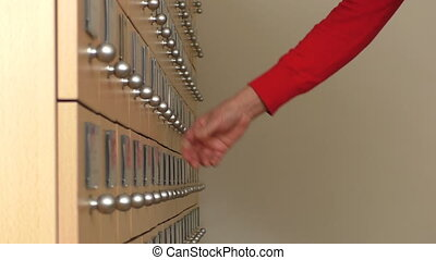 Woman opening card index drawers
