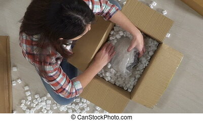Woman opening cardboard box with parcel heart shaped gift box