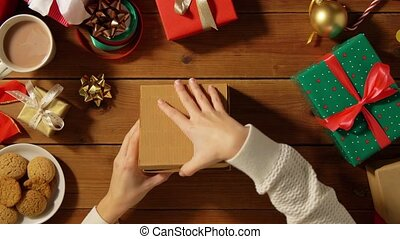 woman opening christmas gift on wooden table - holidays, new...