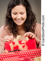 Woman Opening Christmas Gifts At Home