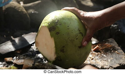 woman opening coconut with big knife - Woman on a public...